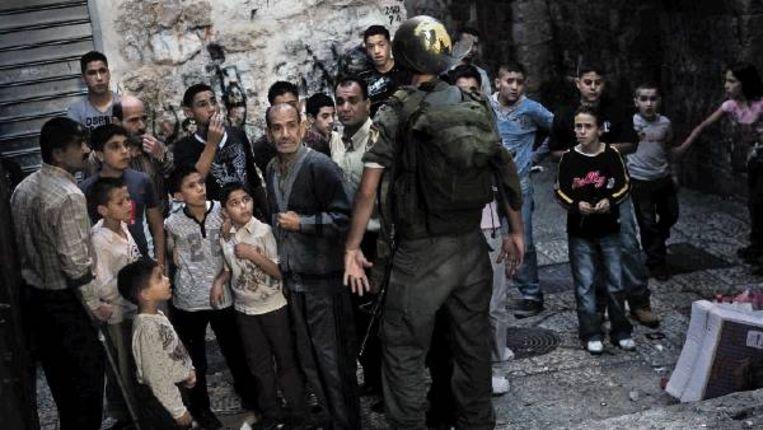 Een Israëlische grenspolitieagent houdt een groep Palestijnen tegen in Jeruzalem. Vandaag zijn er burgemeestersverkiezingen, maar de Palestijnen doen er niet aan mee. (FOTO AP) Beeld