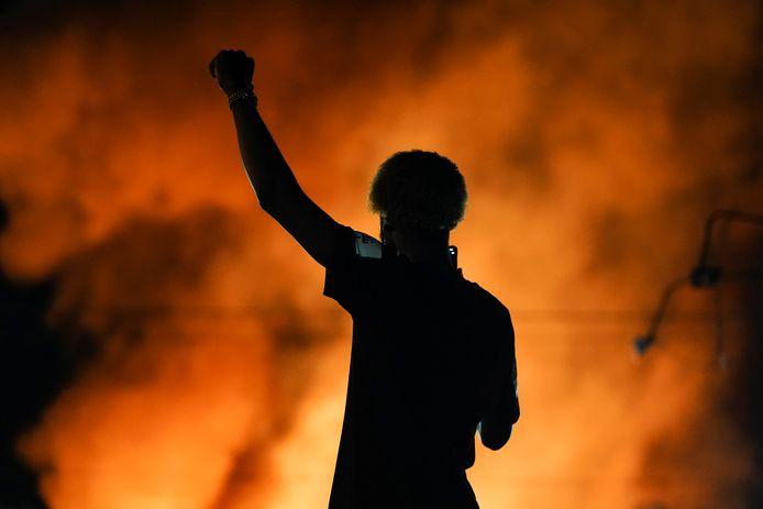 Een demonstrant bij het brandende Wendy's restaurant, waar dit weekend een zwarte man werd doodgeschoten door de politie.