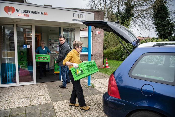 Vrijwilligers van de Drutense voedselbank laden kratten met producten in om rond te brengen. De voedselbankwinkel is gesloten.
