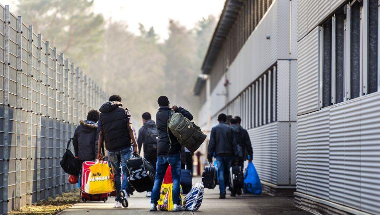 Asielzoekers arriveren bij het nieuw geopende azc in Zeist. Beeld anp