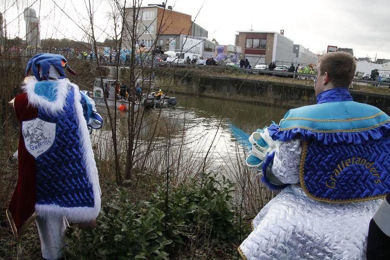 Enkele carnavalisten kijken toe hoe hulpverleners de Dender met een sonarboot doorzoeken.