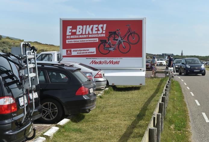 Een vrachtwagen met reclame bij een strandovergang in Domburg, mag dat? Nee, dat mag niet, maar de gemeente Veere deelt zelden boetes uit voor dit soort overtredingen.