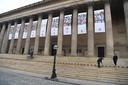 De portretten van de 96 omgekomen Liverpool-fans hangen aan St George's Hall in Liverpool. Op de trappen staan 96 kandelaars.