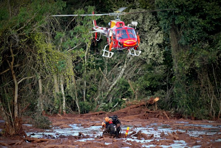 Reddingswerkers trekken een lichaam uit de modder.