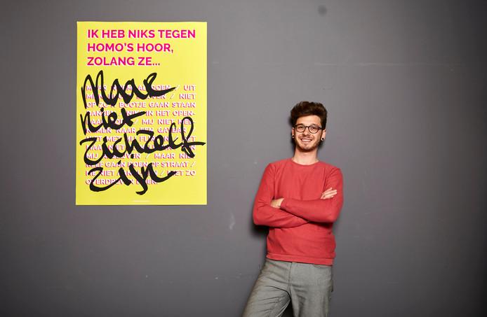 Eerstejaarsstudent Ricardo Abbaszadeh van de Willem de Kooning Academie met een poster die hij ontworpen heeft.