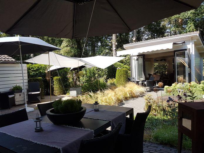 Met een creatie van zonneschermen, parasols, tarp en paraplus komt Wim Velthorst de mooie dagen door.