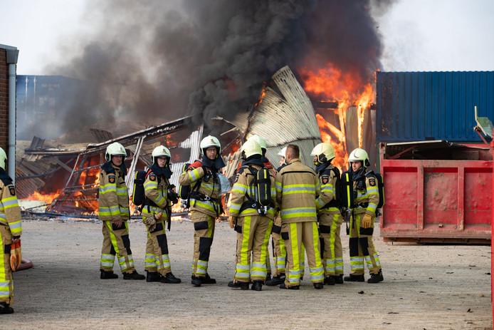 De brandweerlieden overleggen tijdens de brand op het industrieterrein in IJsselmuiden.