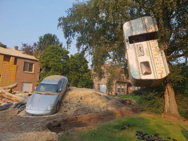 Het wrak van een Porsche, een caravan in een boom en een muur van bierbakken.