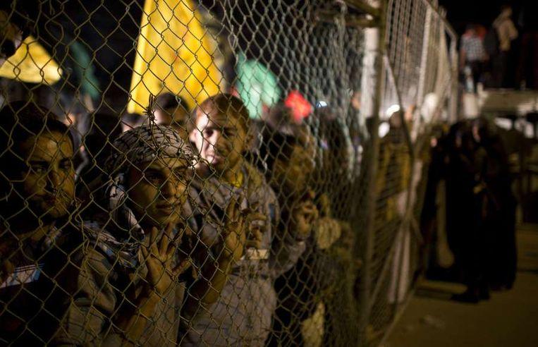 Familieleden wachten de vrijgelaten gevangenen op bij de grens. Beeld afp