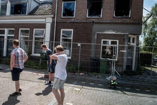 Buurtbewoners leggen bloemen bij het uitgebrande pand in de Emmanuel Murandstraat.