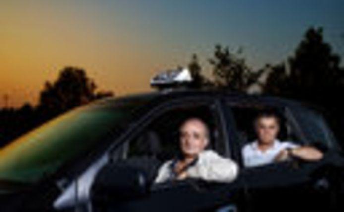 Arthur Evadgian (achter het stuur) en Kia Aziz, toneelspeler en filmmaker - maar ook allebei ex-vluchteling en taxichauffeur. Omdat er niks anders op zit, voorlopig.