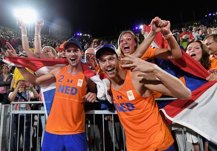 Brouwer (rechts) en Meeuwsen vieren hun brons met Nederlandse fans op het strand van de Copacabana. Beeld getty