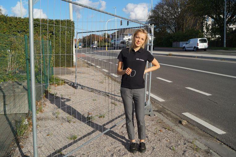 Sales manager Charlotte van HB Classics bij het hek in de Pittemsesteenweg, waar de promobanner werd verwijderd door onbekenden.