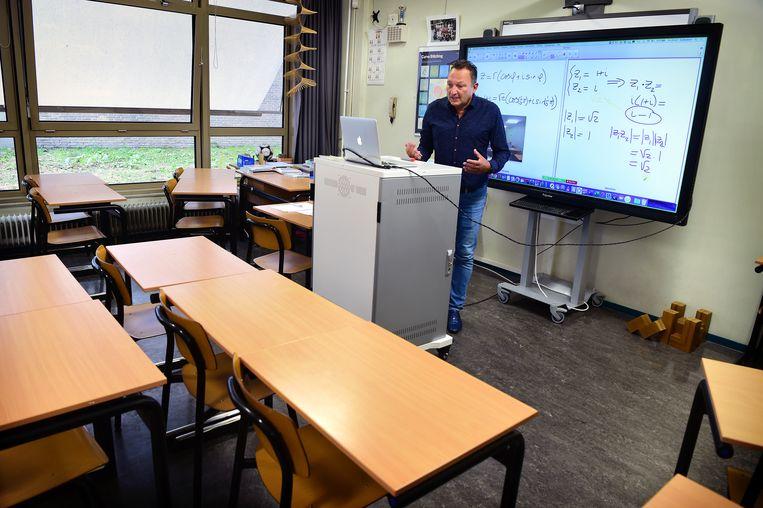 Wiskundeleraar Hub Kusters doceert vanuit een leeg lokaal in Hoensbroek. Beeld Marcel van den Bergh / de Volkskrant