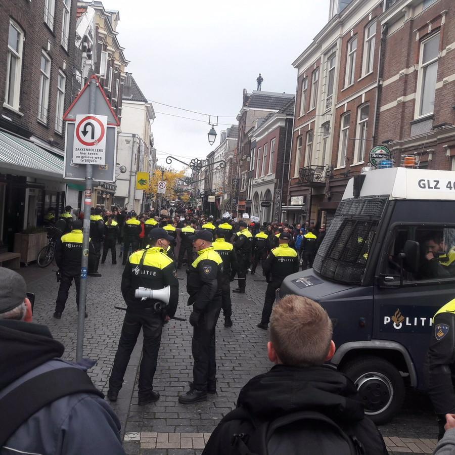 Politie dringt de linkse demonstranten de Lange Hezelstraat in.