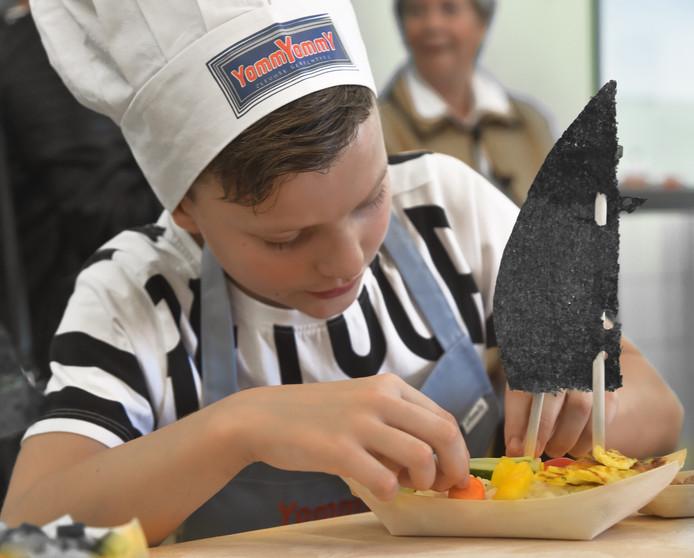 Sam Groothedde van de Kinderkooktuin maakt zijn 'sushi in een bootje' af.