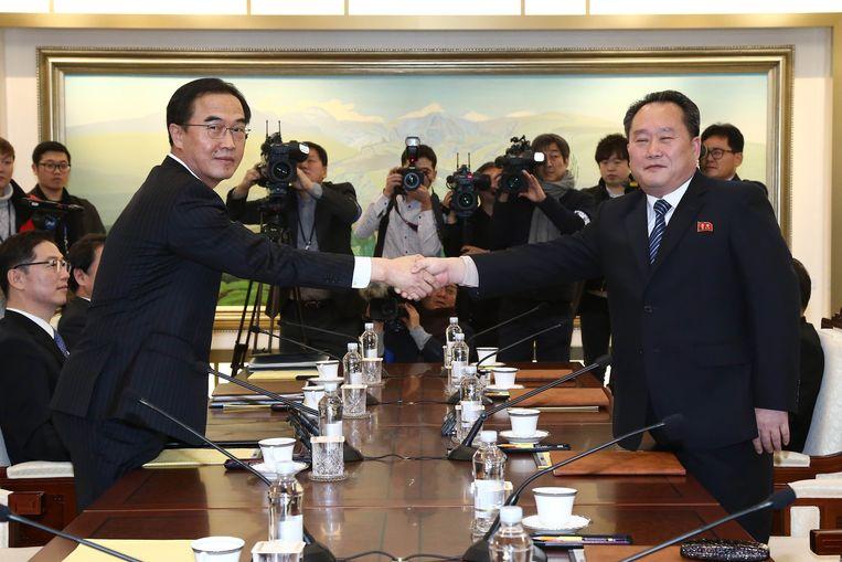 De Noord-Koreaanse delegatieleider Ri Son-gwon (rechts) en zijn Zuid-Koreaanse ambtsgenoot Cho Myoung-gyon schudden elkaar de hand aan de onderhandelingstafel.