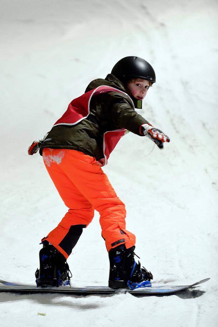 Pepijn komt al sierlijk de helling af met zijn snowboard tijdens de snowboardles.