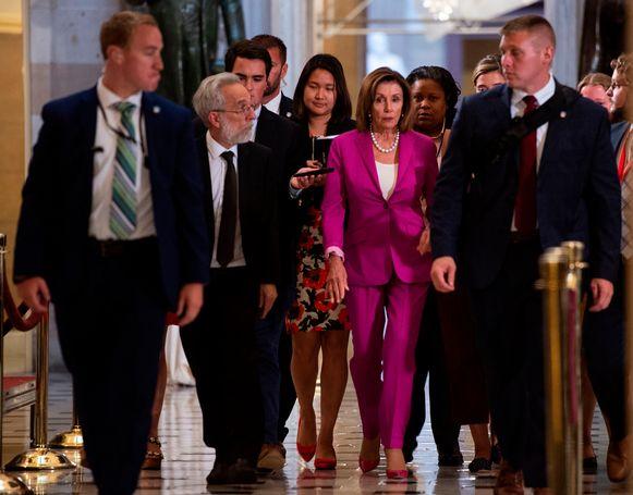 Speaker of the House of Representatives Nancy Pelosi omringd door journalisten voor de stemming.