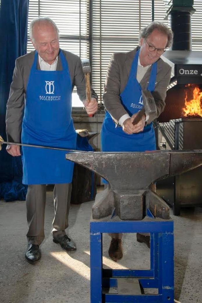 Burgemeester Ton Rombouts en Ad 's-Gravesande van stichting Jheronimus Bosch 500 slaan de eerste hamerslagen op het gloeiende metaal.