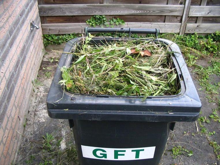 Een GFT-bak gevuld met te veel afval dat afkomstig is uit de tuin.