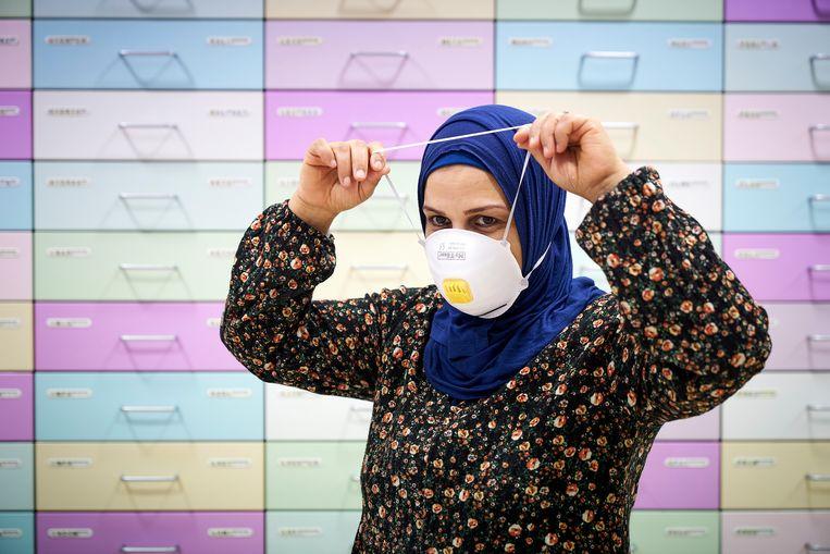 Een werknemer van de apotheek demonstreert een mondkapje.  Beeld ANP