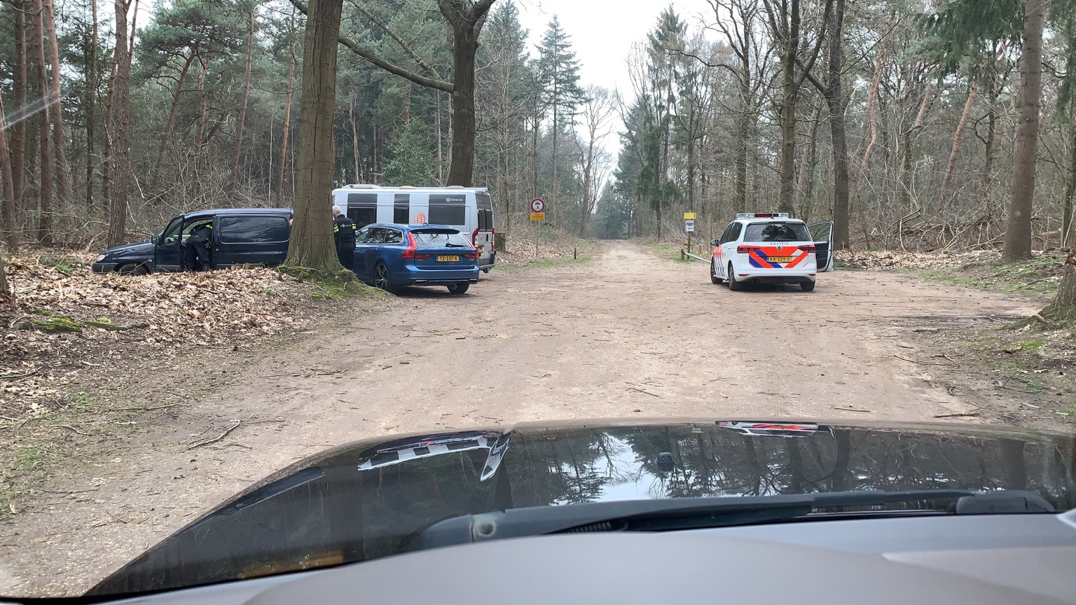 Agenten doorzoeken in het bos het blauwe bestelbusje van de belager van Van Lent. DG