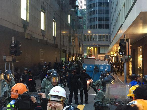 De politie heeft enkele tientallen protestanten samengedreven in een steegje (links achter de container). Het publiek en de pers worden op afstand gehouden.