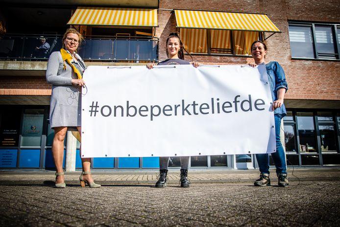 Jolanda Koning, Nikki en Angelique van Wijk houden het spandoek omhoog in 's-Gravendeel.