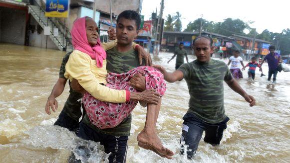 Militairen dragen een vrouw naar een veilige plek.