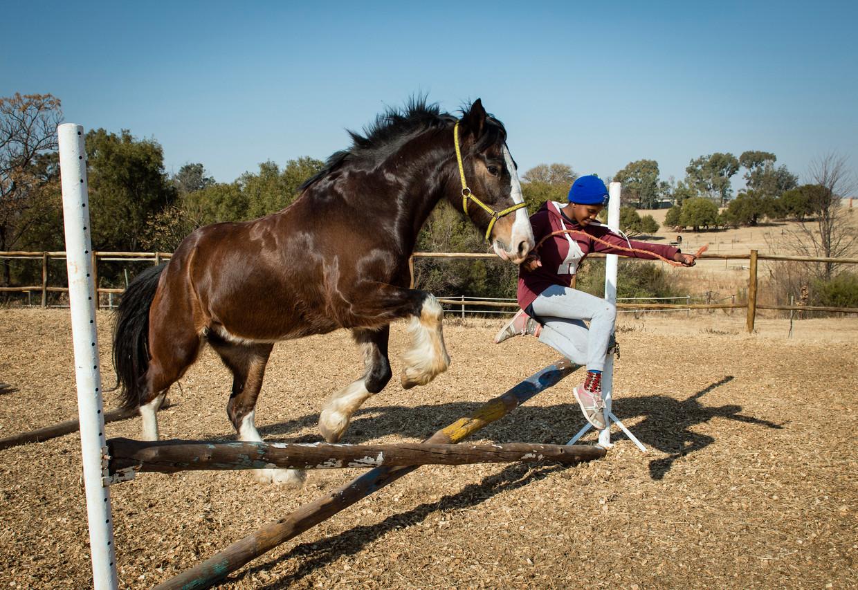 Katlego springt met een van de paarden over een hindernis.