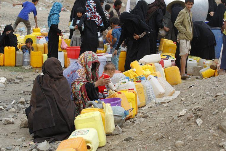 Inwoners van Sanaa vullen jerrycans met water. De watertoevoer in de stad is verstoord vanwege de aanhoudende aanvallen. Beeld anp