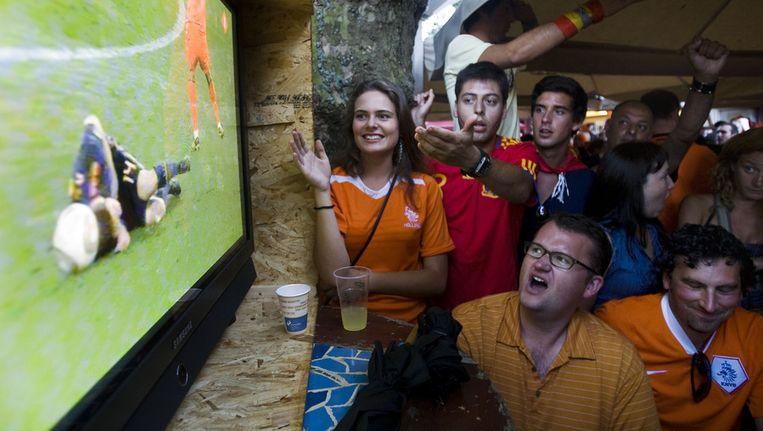 Nederlandse en Spaanse fans kijken in een cafe op het Thorbeckeplein in Amsterdam naar de WK-finale tussen Nederland en Spanje. (Archieffoto) Beeld null