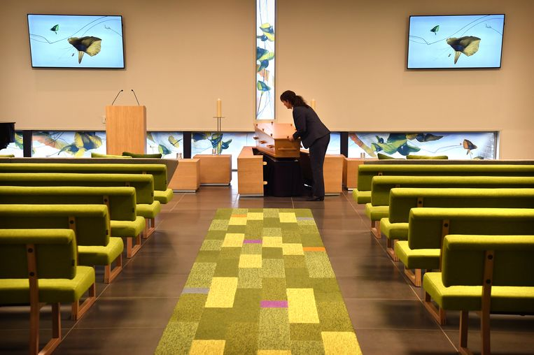 Een medewerkster van een crematorium laat de handelingen zien van het plaatsen van de kist (in deze geen dode). Beeld Marcel van den Bergh