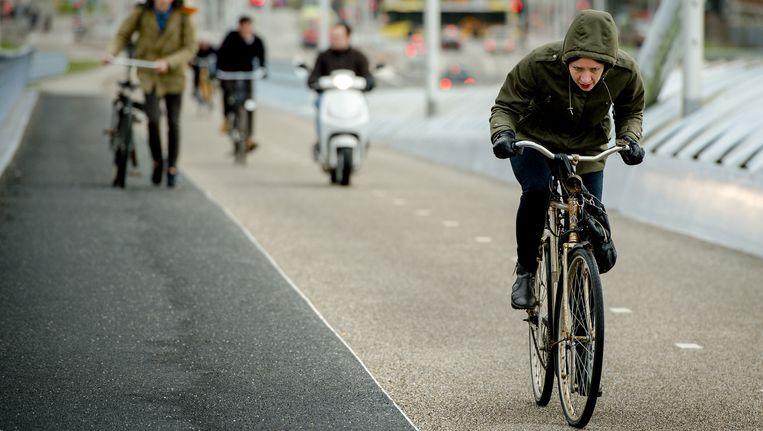 Fietsers trotseren de harde wind op een brug in Utrecht Beeld anp