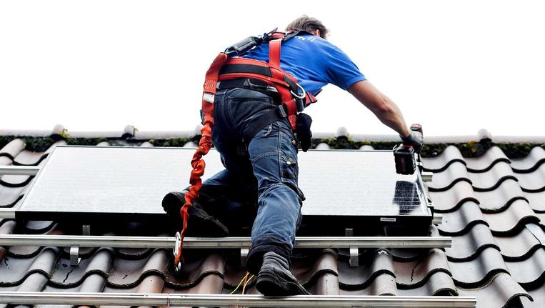 Een monteur plaatst zonnepanelen op het dak van een woonhuis. Beeld ANP