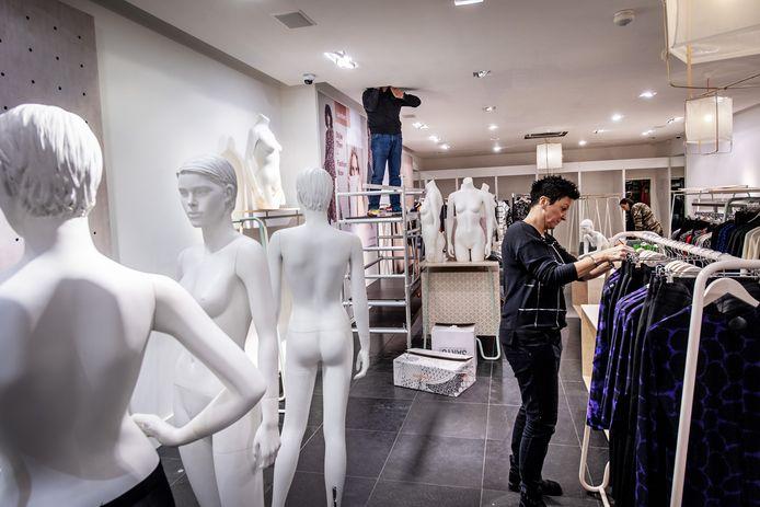 Verkoopster Brenda hangt de collectie aan de rekken van Sandwich, de vernieuwde kledingwinkel in de Marikenstraat in Nijmegen.