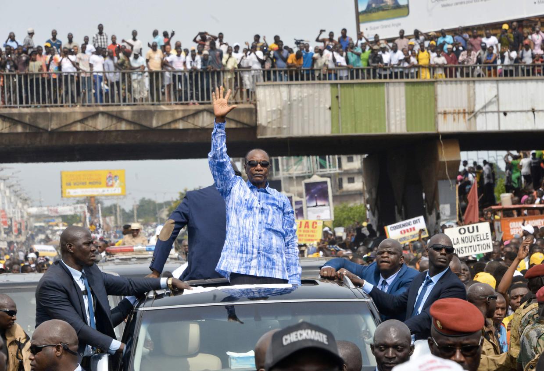 President Alpha Condé rijdt door de straten van Conakry.  Beeld null