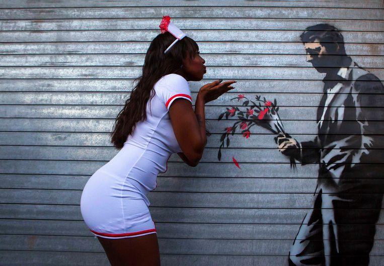 Een voorbijgangster reageert op een kunstwerk van Banksy op een winkelrolluik in New York.