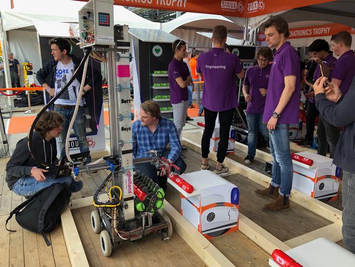 Studenten testen hun robots uit op de baan waarop lege batterijen moeten worden verwisseld voor volle.