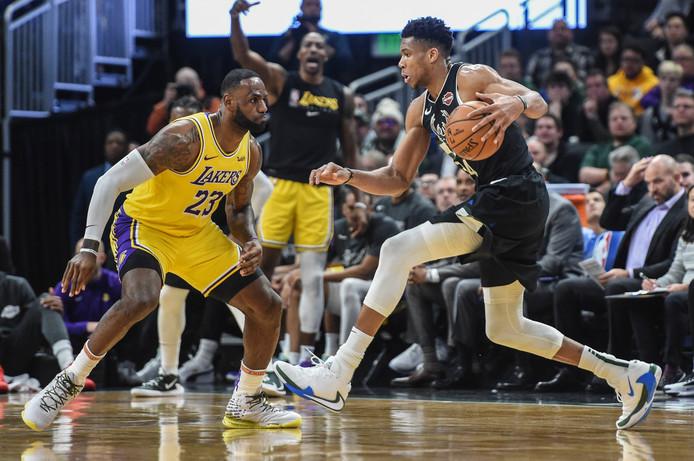 Giannis Antetokounmpo (r) in duel met LeBron James tijdens de wedstrijd tussen de Lakers en de Bucks dit seizoen.