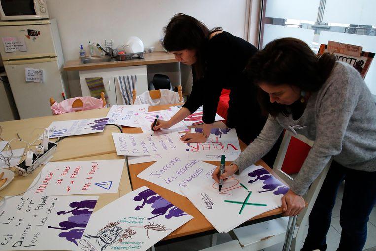 Alix Chazeaux-Guibert (links) en Celinne Piques (rechts) van de feministische organisatie 'Osons le Feminisme' bereiden posters voor. Beeld AP