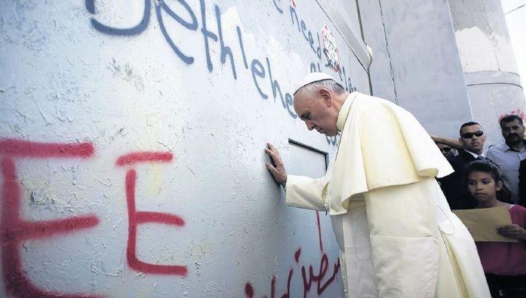Paus Franciscus bij de afscheidingsmuur die op de Westelijke Jordaanoever staat. Beeld epa