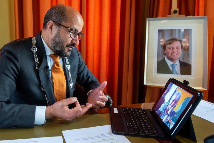 Burgemeester Ahmed Marcouch in een videogesprek met één van de Arnhemmers die vandaag tot Ridder of Lid in de Orde van Oranje-Nassau zijn benoemd.