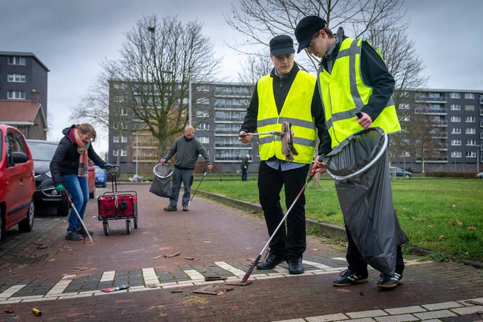 Mensen van de Stichting Heel Arnhem Schoon ruimen restanten van vuurwerk op na de jaarwisseling.