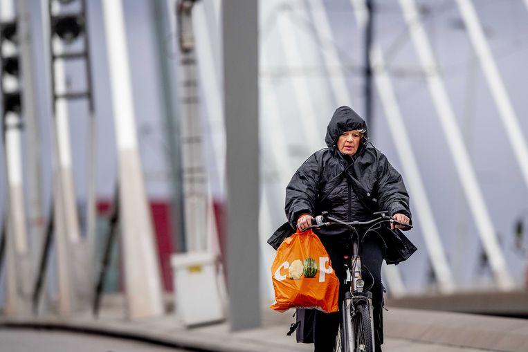 Een fietser rijdt tegen de wind in over de Erasmusbrug. Beeld ANP