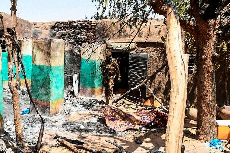 Een soldaat loopt door de ruines van het dorpje Ogossagou in Mali.