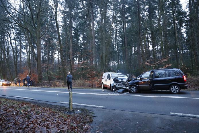De twee auto's botsten frontaal op elkaar in Epe. Links in beeld de derde auto die gekanteld in de berm ligt.