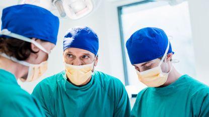 Anesthesist en chirurg vechten met elkaar terwijl hun patiënt op operatietafel ligt