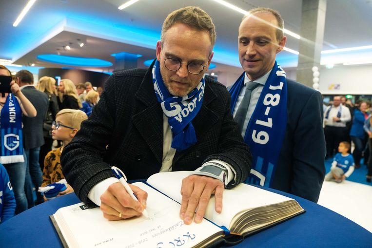 Burgemeester Wim Dries en voorzitter van KRC Genk Peter Croonen, die het gulden boek van de stad tekent.